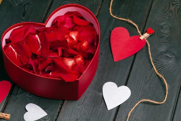 Beaucoup de pétales de rose à l'intérieur d'une boîte cadeau ouverte sur du vieux bois