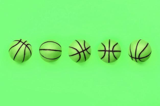 Beaucoup de petites balles vertes pour le sport de basketball se trouvent sur