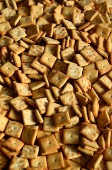 Beaucoup de petits biscuits sont de forme carrée. un motif d'un biscuit salé jaune. image de fond avec une pâte salée