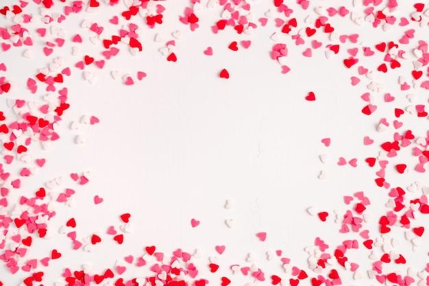 Beaucoup de petits coeurs rouges, roses et blancs sur fond clair