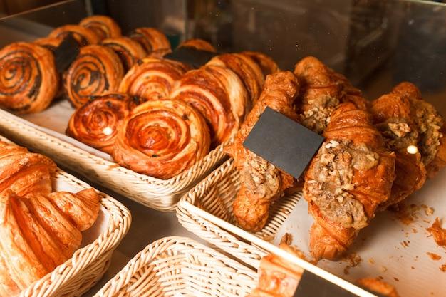 Beaucoup de petits pains et croissants sur une étagère d'une boulangerie