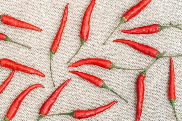 Beaucoup de petits piments rouges chauds gros plan jettent dans un ordre aléatoire sur textile un sac naturel