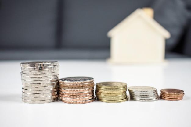 Beaucoup de pièces de monnaie pour acheter une maison sur une table blanche. économiser de l'argent.