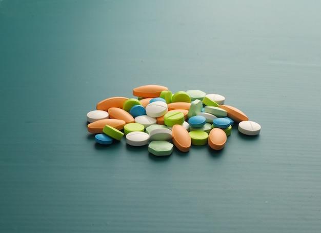 Beaucoup de pilules colorées sur fond vert
