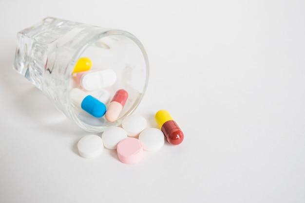 Beaucoup de pilules colorées renversant de minuscule verre sur fond blanc