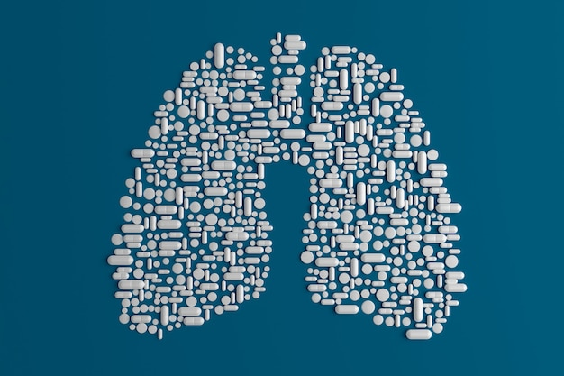 Beaucoup de pilules dispersées sur un bleu en forme de poumon