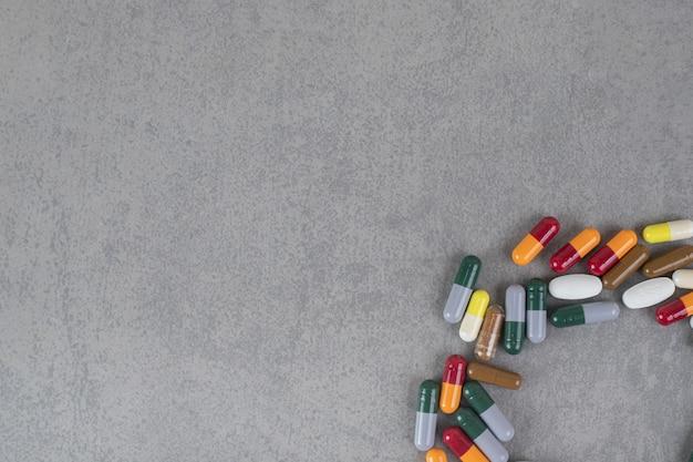 Beaucoup de pilules mélangées colorées sur une surface grise
