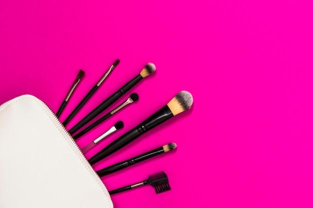 Beaucoup de pinceaux de maquillage en sac blanc sur le fond rose