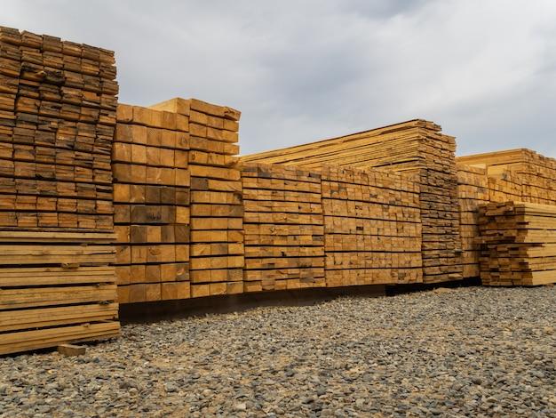 Beaucoup de planches empilées les unes sur les autres dans l'entrepôt. bois de construction pour une utilisation ultérieure dans la construction
