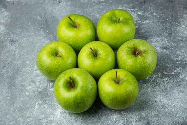 Beaucoup de pommes mûres sur du marbre.