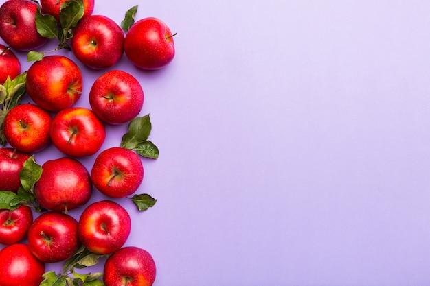 Beaucoup de pommes rouges sur fond coloré, vue de dessus. motif d'automne avec pomme fraîche au-dessus de la vue avec espace de copie pour la conception ou le texte.
