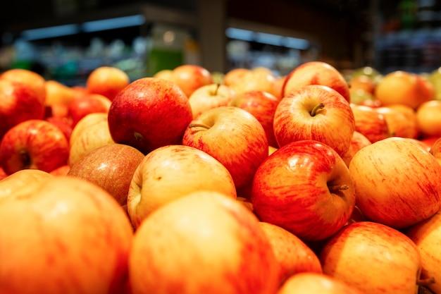 Beaucoup de pommes rouges juteuses brillantes sur le comptoir.
