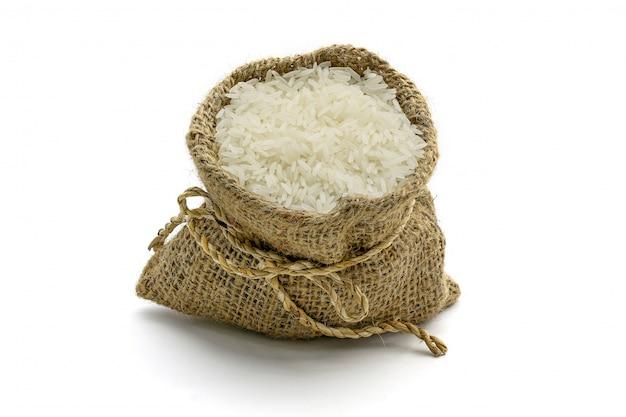 Beaucoup de riz au jasmin en sac, isolé sur une surface blanche