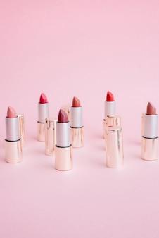 Beaucoup de rouges à lèvres de luxe en or dans différentes nuances de support rose