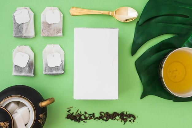 Beaucoup de sachet de thé avec des cubes de sucre et une boîte sur fond vert
