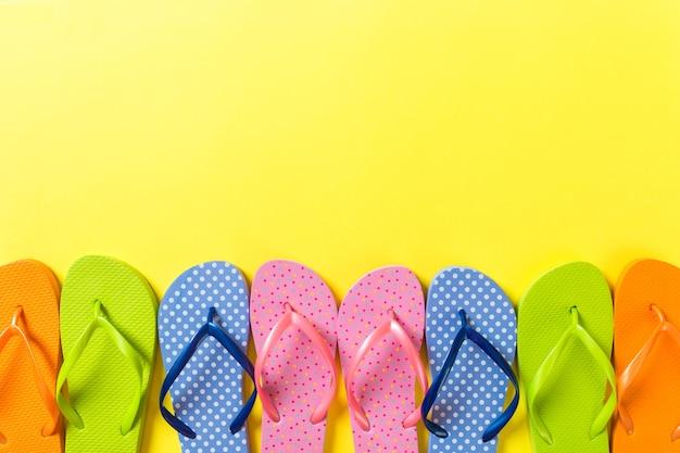 Beaucoup de sandales colorées à bascule, vacances d'été sur fond coloré, vue de dessus de l'espace de copie.