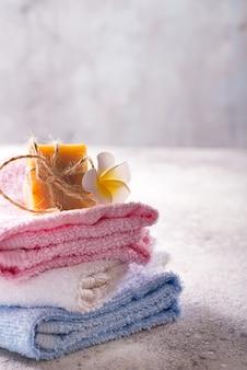 Beaucoup de serviettes de bain colorées empilées les unes sur les autres avec du savon pour les mains et des fleurs sur une pierre claire, fond