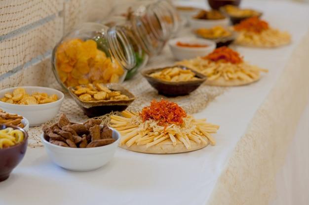 Beaucoup de snacks salés sur une table, beaucoup de fromage et des craquelins sur la table avec des snacks