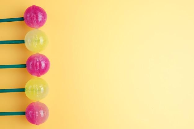Beaucoup de sucettes colorées sur la gauche. sucette sur fond jaune. copier l'espace pour le texte.