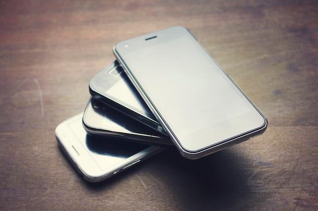 Beaucoup de téléphones intelligents sur la table en bois