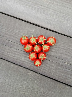 Beaucoup de tomates cerises sur une surface en bois sombre