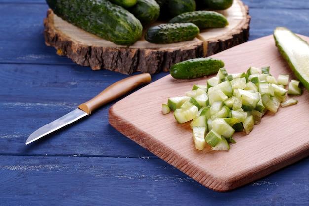 Beaucoup de tranches de concombre hachées sur une planche à découper avec un couteau sur une table en bois bleue