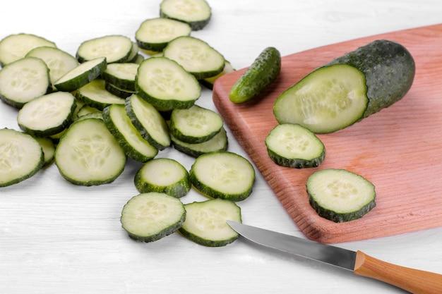 Beaucoup de tranches de concombre sur une planche à découper avec un couteau sur une table en bois blanc