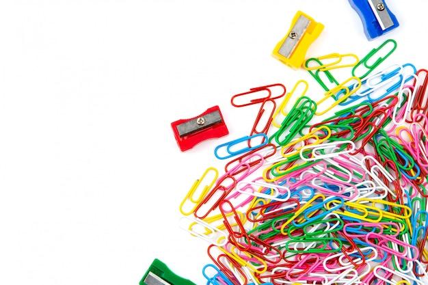 Beaucoup de trombones colorés et de taille-crayons sur fond blanc. vue de dessus et espace de copie.