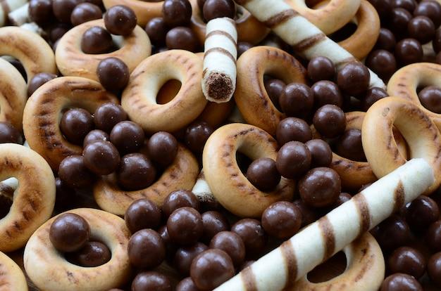 Beaucoup de tubules sucrés croustillants, de boules de chocolat fondant et de bagels jaunes reposent sur une surface en bois. vue rapprochée