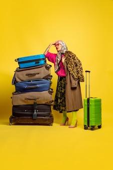 Beaucoup de vêtements pour voyager. portrait de femme caucasienne sur espace jaune