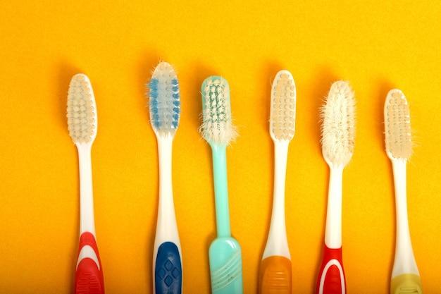 Beaucoup de vieilles brosses à dents disposées sur fond jaune