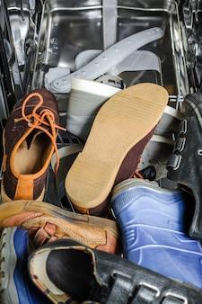 Beaucoup de vieilles chaussures chargées dans le lave-vaisselle.