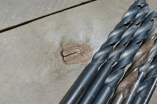 Beaucoup de vieilles perceuses se trouvent sur un fond en bois de planche. fermer.