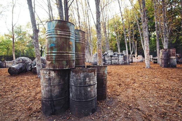 Beaucoup de vieux barils ronds à la base pour jouer au paintball et derrière lesquels se cachent les joueurs excités par le jeu