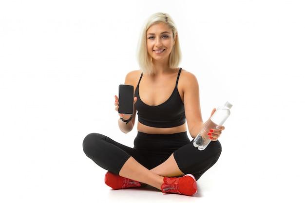 Beauiful sport caucasian girl est assis sur le plancher, les jambes croisées, montre un téléphone mobile et garde une bouteille d'eau isolée