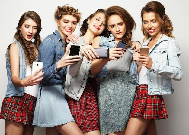 Beauté, amitié, jeunesse et technologie. portrait en studio de cinq magnifiques jeunes femmes prenant selfie.