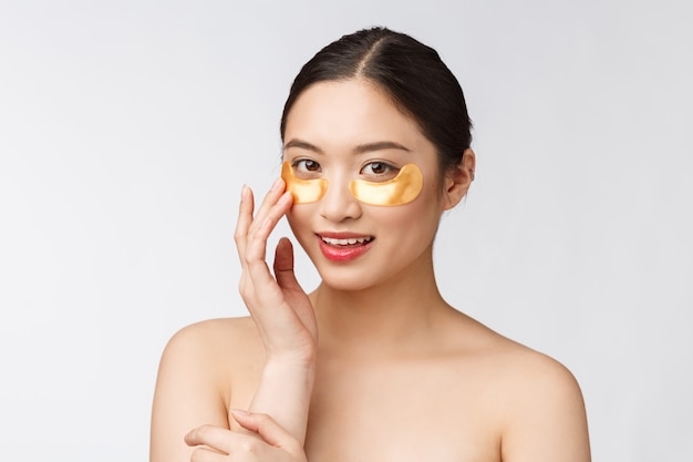 Beauté asiatique adolescent femme soin de sa peau avec des masques pour les yeux d'or sous les yeux