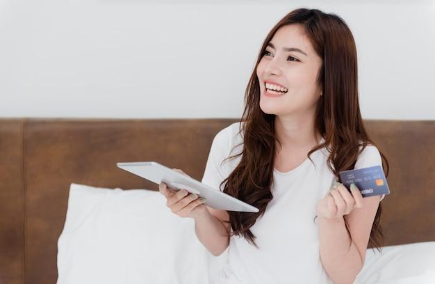 Beauté asiatique femme utiliser une carte de crédit pour faire des achats à l'aide d'une tablette via internet avec un visage souriant heureux