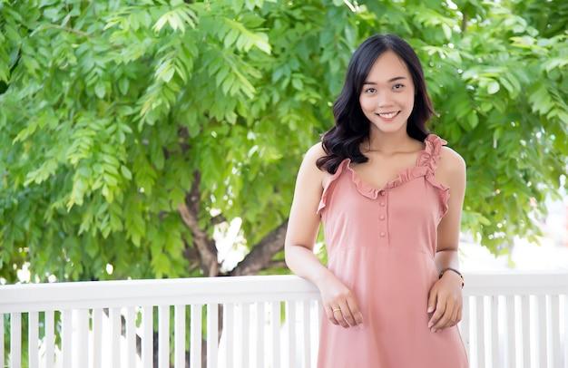 Beauté asiatique fille sourire action sur balcon à la maison avec arbre