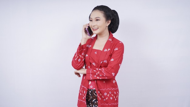 Beauté asiatique en kebaya au téléphone via smartphone isolé sur fond blanc