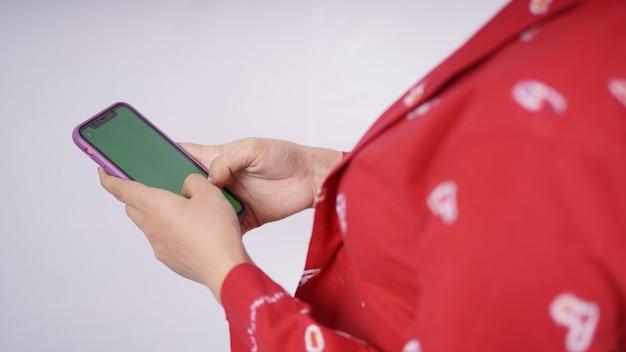 Beauté asiatique en kebaya joue smartphone isolé sur fond blanc