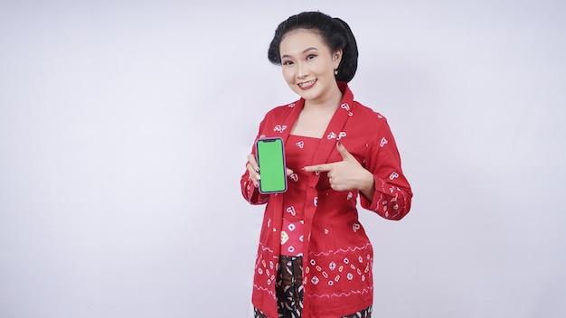 Beauté asiatique en kebaya montrant l'écran du smartphone isolé sur fond blanc