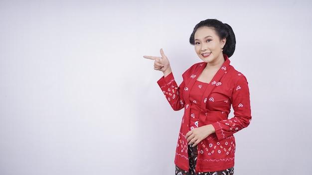 Beauté asiatique en kebaya pointant vers le côté blanc isolé sur fond blanc