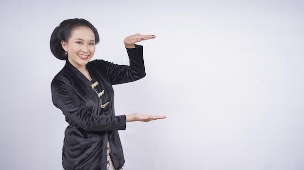 Beauté asiatique en kebaya pointant vide isolé sur fond blanc