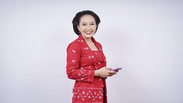 Beauté asiatique en kebaya rit avec smartphone isolé sur fond blanc