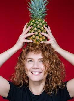 Beauté aux cheveux roux dans un t-shirt noir avec une impression de coeur tenir un ananas dans ses mains sur un espace rouge