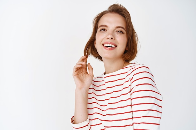 Beauté. belle fille impertinente riant coquette, jouant avec les cheveux courts et souriante, debout en blouse rayée contre le mur blanc
