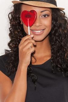 Beauté avec des bonbons. jeune femme africaine espiègle au chapeau funky tenant des bonbons en forme de coeur devant ses yeux et souriant en se tenant debout sur fond blanc