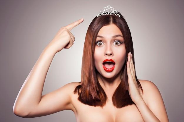 Beauté bouchent le portrait d'une femme brune avec du rouge à lèvres rouge. diadème de couronne de diadème sur elle.