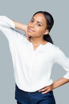Beauté confiante. jolie jeune femme africaine tenant les mains sur la hanche et regardant la caméra en se tenant debout sur fond gris